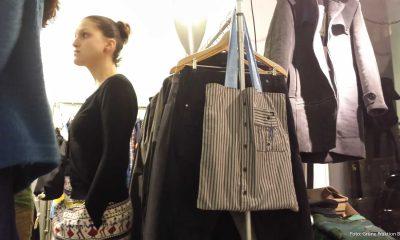Auf dem Bild ist eine Frau und verschiedene Kleider zu sehen.