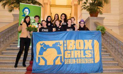 Auf dem Bild ist eine Gruppe von Box-Girls-Berlin-Kreuzberg zu sehen, die mit einem Transparent für die Kamera posieren.