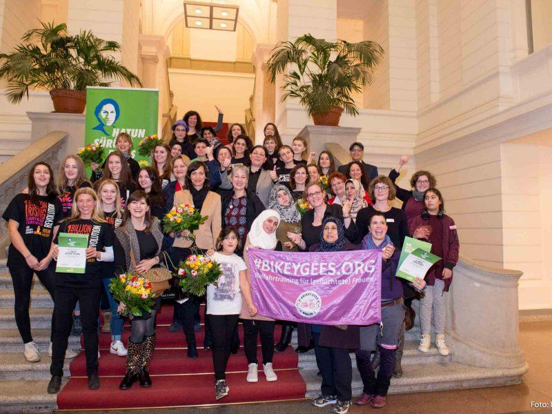 Auf dem Bild ist eine Gruppe von Gewinnerinnen zu sehen, die für die Kamera posieren.