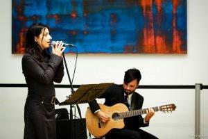 Auf dem Bild ist eine Frau zu sehen, die singt. Im Hintergrund spielt ein Mann Gitarre.