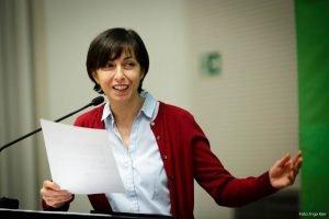 Auf dem Bild ist eine Frau zu sehen, die eine Rede hält.