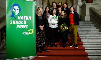Frauen posieren auf einer Treppe neben einem Plakat des Hatun-Sürücü-Preises.