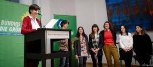 Auf dem Bild ist zu sehen, wie eine Frau eine Rede hält. Im Hintergrund stehen einige andere Menschen.