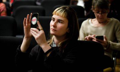 Auf dem Bild ist eine Frau zu sehen, die ein Handyfoto macht.