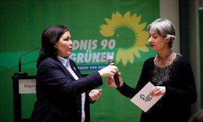 Auf dem Bild sind Susanna Kahlefeld und Anja Kofbinger zu sehen, die sich das Mikro übergeben.