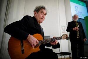Auf dem Bild ist ein Gitarrist zu sehen, der Gitarre spielt. Im Hintergrund steht ein Mann mit einem Mikrofon.