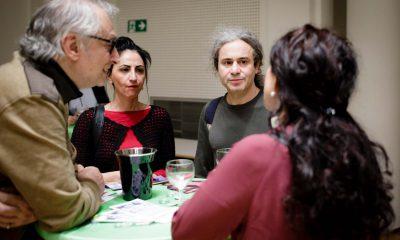 Auf dem Bild sind zwei Frauen und zwei Männer zu sehen, die an einem Tisch stehen.
