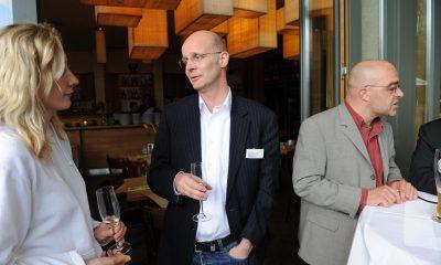 Auf dem Bild sind drei Personen zu sehen, die sich unterhalten.