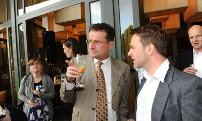 Auf dem Bild sind zwei Männer zu sehen, die sich unterhalten. Im Hintergrund stehen weitere Personen.