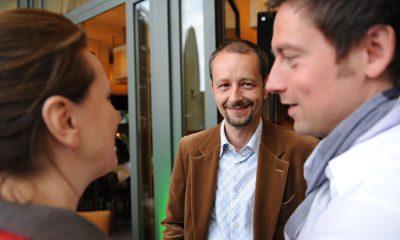Auf dem Bild sind 3 Personen zu sehen, die sich unterhalten.