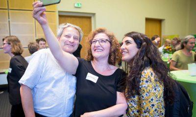 Auf dem Bild ist Fatos Topac zu sehen, die mit zwei anderen Personen ein Selfie macht.