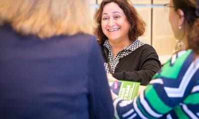 Auf dem Bild ist eine lachende Frau im Stehkreis mit anderen Frauen zu sehen.