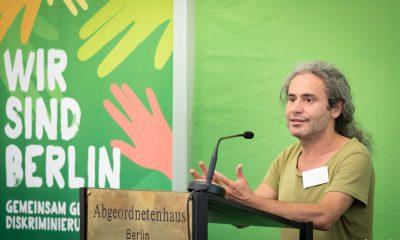 Auf dem Bild ist Turgut Altug am Pult zu sehen, während er eine Rede hält.