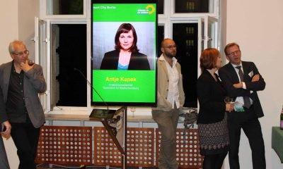 Auf dem Bild ist ein Portrait von Antje Kapek auf einem Bildschirm zu sehen. Im Hintergrund stehen einige Menschen.