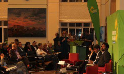 Auf dem Bild ist eine Podiumsdiskussion und das zugehörige Publikum zu sehen.