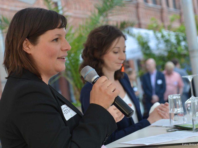 Auf dem Bild hält Antje Kapek eine Rede, im Hintergrund steht Ramona Pop.