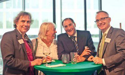 Auf dem Bild sind vier Personen zu sehen, die lachen und für die Kamera posieren.