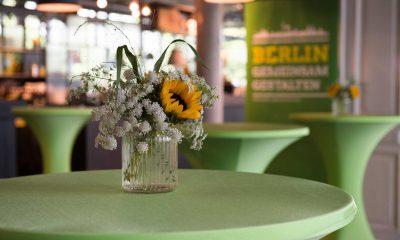 Auf dem Bild sind grüne Stehtische zu sehen, die mit Blumen geschmückt sind.