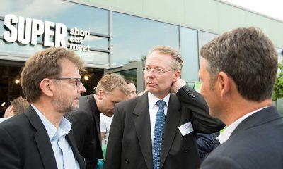 Auf dem Bild sind drei Männer zu sehen, die sich unterhalten.