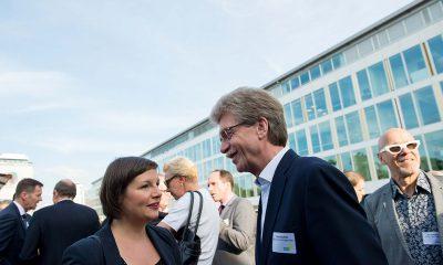 Auf dem Bild sind Antje Kapek und ein Mann zu sehen. Im Hintergrund stehen andere Personen.
