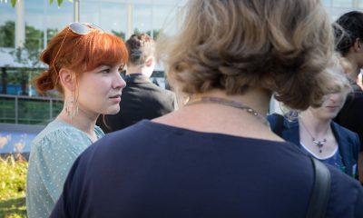 Auf dem Bild ist eine Frau zu sehen, die sich mit anderen Frauen unterhält.
