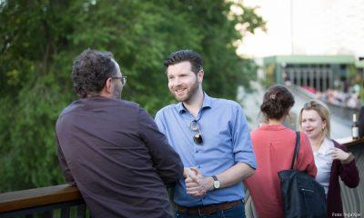 Auf dem Bild sind zwei Männer und zwei Frauen zu sehen, die sich unterhalten.