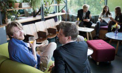 Auf dem Bild sind zwei Männder zu sehen, die in Richtung der Kamera gucken. im Hintergrund unterhalten sich drei andere Personen.