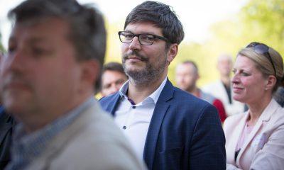 Auf dem Bild ist der Senator Dirk Behrendt zu sehen. Im Vorder- und Hintergrund sind noch einige andere Personen.