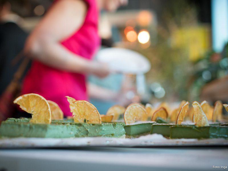 Auf dem Bild sind grüne Kuchen zu sehen, die mit Orangenscheiben garniert sind.