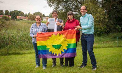 Auf dem Bild posieren vier Personen mit einer Regenbogenflagge.