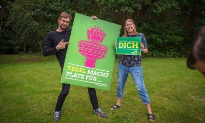 Auf dem Bild posieren zwei Abgeordnete mit einem Plakat gegen den Weiterbetrieb des Flughafens Tegel. (Stefan Gelbhaar und June Tomiak)