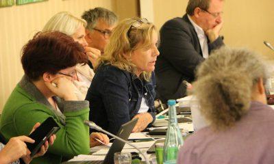 Auf dem Bild sind einige Abgeordnete zu sehen, während sie an Sitzungstischen sitzen.