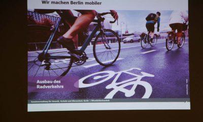 Auf dem Bild ist ein Beamerbild zu sehen, auf dem Menschen Rad fahren.