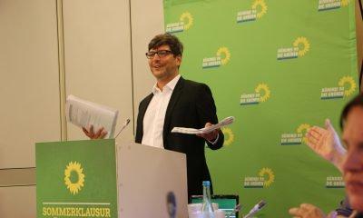 Auf dem Bild ist Dirk Behrendt zu sehen, der an einem Pult steht und redet.