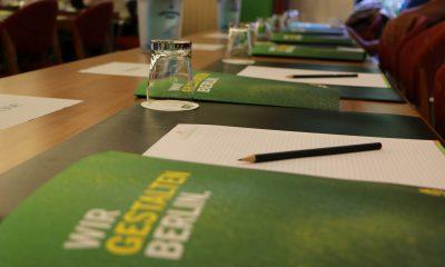 Auf dem Bild sind grüne Flyer zu sehen.