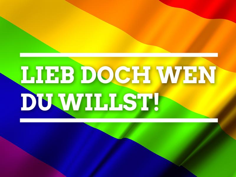 Eine sechsfarbige Regenbogenfahne, auf der folgender Satz steht: Lieb doch wen du willst.
