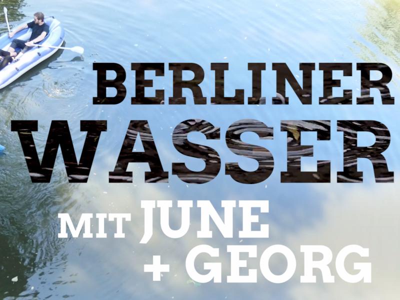 """Ein aufblasbares Boot ist auf der Spree. Darin sitzen die Abgeordneten June Tomiak und Georg Kössler. Daneben schwimmt ein blauer aufblasbarer Delfin. Auf der Wasserfläche daneben ist der Text """"Berliner Wasser mit June und Georg"""" zu lesen."""