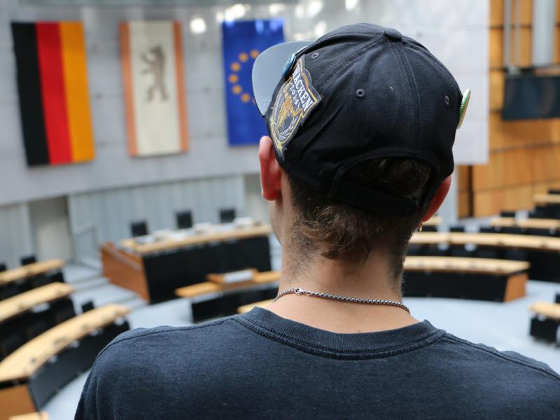 Auf dem Bild ist ein junger Mann von hinten zu sehen, der auf der Besuchertribüne des Plenarsaals im Berliner Abgeordnetenhaus steht.