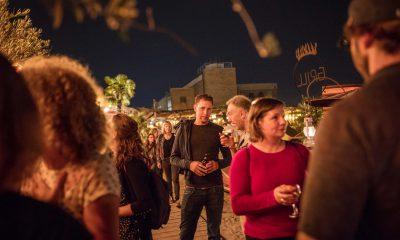 Auf dem Bild sind verschiedene Menschen in einer Strandbar in Hamburg zu sehen.