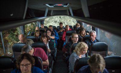 Auf dem Bild sind verschiedene Leute in einem Bus zu sehen.