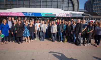 Auf dem Bild sind die Abgeordneten und Mitarbeiter der Grünen Abgeordnetenhausfraktion zu sehen, die vor einem Elektrobus stehen, um ein Gruppenbild zu machen.