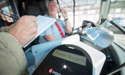 """Auf dem Bild ist ein Busfahrer zu sehen und eine Person, die sich mit ihm unterhält und Notizen macht. Auf einem Display des Busses steht """"Guten Morgen""""."""