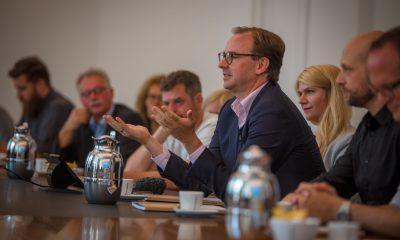 Auf dem Bild sind verschiedene Personen zu sehen, die in einem Sitzungssaal sitzen.