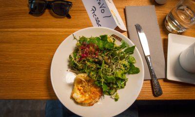 Auf dem Bild ist ein Teller mit Salat und einem Ziegenkäse zu sehen.