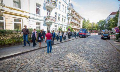 Auf dem Bild ist eine Gruppe von Menschen beim Gehen über einen Bürgersteig zu sehen.