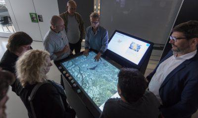 Verschiedene Menschen stehen um einen Bildschirm, mit dem Städte- und Projektplanung vereinfacht werden soll.