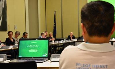 Auf dem Bild sieht man einen Diskussionsteilnehmer von hinten