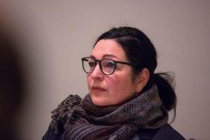 Auf dem Bild ist Astrid Passin zu sehen, die Sprecherin der Hinterbliebenen der Opfer des Terroranschlags. Sie sitzt auf dem Podium.