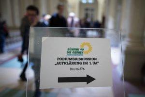 Auf dem Bild ist ein Schild zu sehen, das den Weg zur Podiumsdiskussion zeigt.