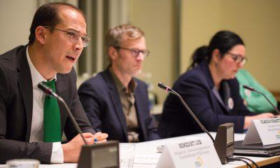 Auf dem Bild ist Benedikt Lux auf dem Podium zu sehen, während er redet.